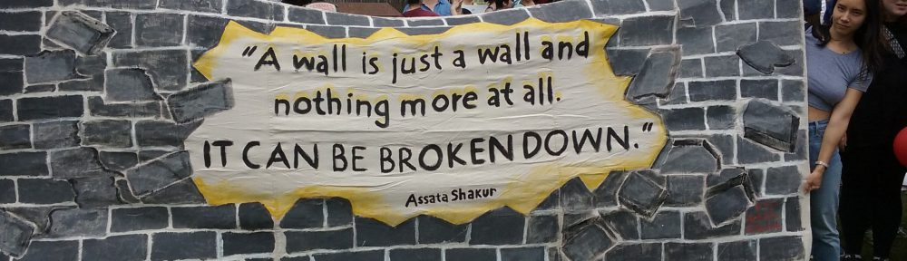 """Protestors holding sign that reads """"A wall is just a wall and nothing more at all. It can be broken down."""""""
