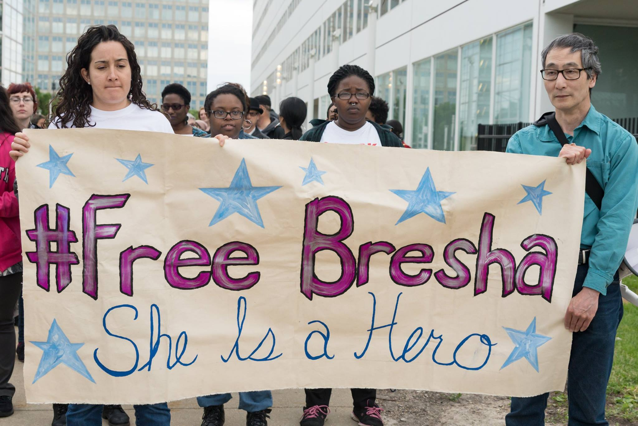 Protestors holding a sign reading #FreeBesha, She Is a Hero