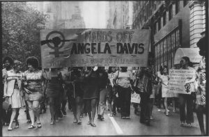 "Members of the Third World Women's Alliance marching with a banner that reads ""Hands Off Angela Davis"""