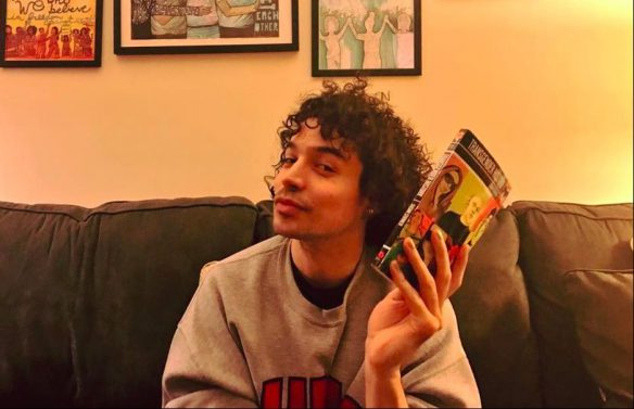 Benji Hart sitting on a couch holding a book in left hand