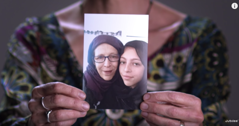 Hands holding a photo of a Muslim mother and daughter