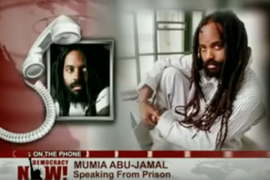 Photo of Mumia Abu-Jamal on Democracy Now! being interviewed by phone
