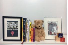 bookshelf with blocks, teddy bear, a photo of Angela Davis and radical children's books.