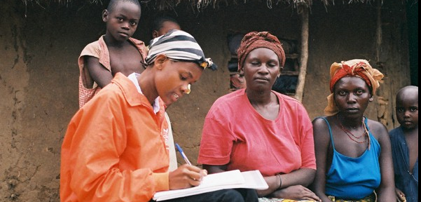 Researcher sitting and interviewing a group of refugees in Uganda