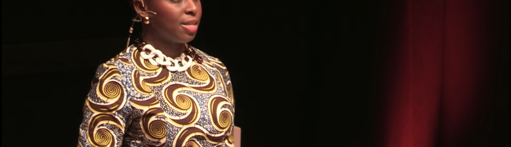 Chimamanda Ngozi Adiche on stage in front of podium