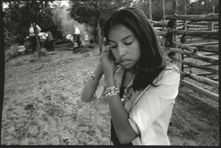 Black and white photograph of Navajo girl putting on earring