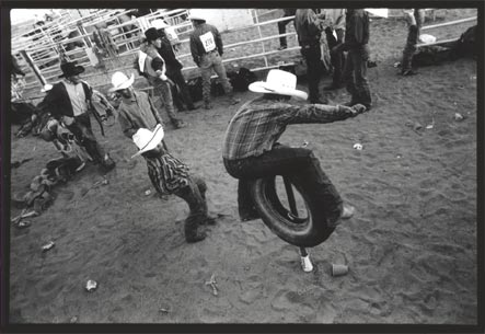 Black and white photograph at a rodeo with a man simulating riding a bull on a tire