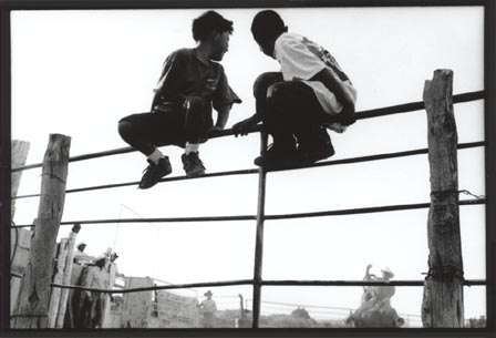 Black and white photograph of two boys sitting on a fence