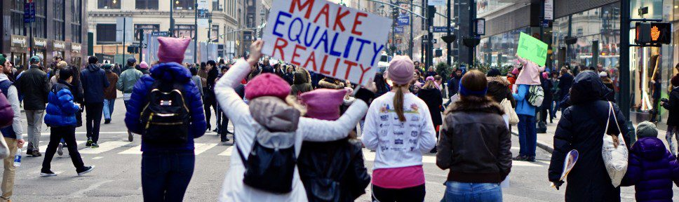"Protestors marching, holding sign that reads ""Make Equality Reality"""