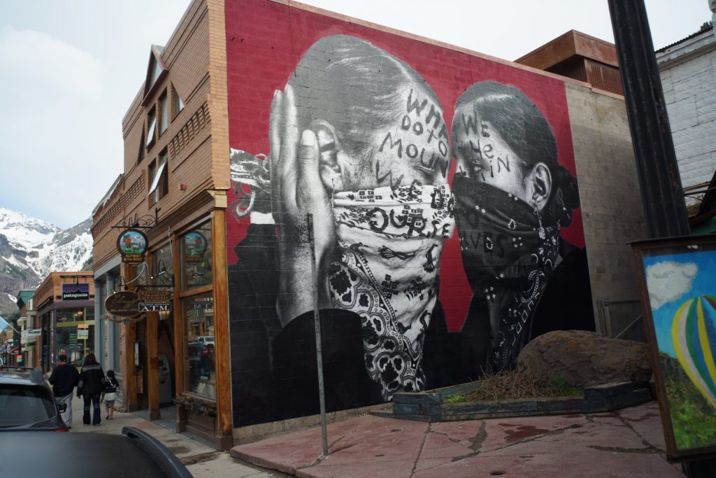 Photograph of large mural on the side of a building with two indigenous figures with bandanas covering their face