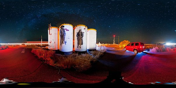 Night time photograph of large murals of Navajo people on big white tubes