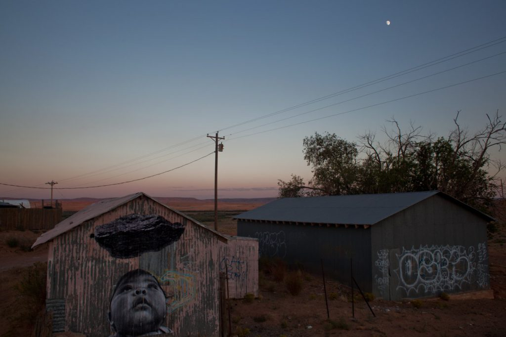 Sunset photograph of mural on small house of a baby looking up a cloud