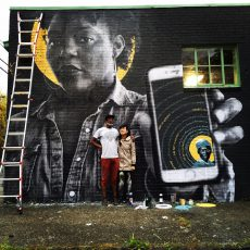 Photograph of artist in front of large scale mural of black woman holding up an iPhone