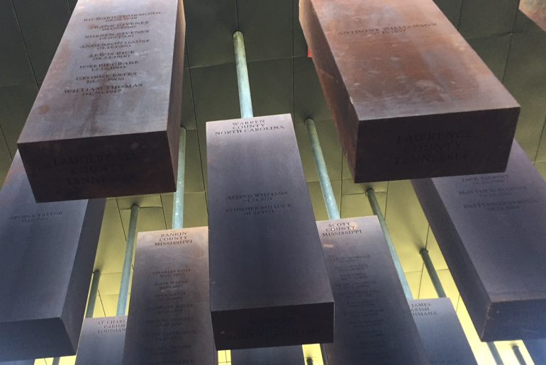 National Memorial for Peace and Justice, metal rectangles hanging from the ceiling with the locations of documented lynchings and the names of the victims