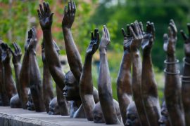 National Memorial for Peace and Justice, copper statues of black people raising their arms, heads just above concrete