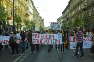 "protesters in street carrying banner that says ""Freedom for Education"""