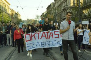 "Protesters in street carrying a banner in Hungarian that says ""Taught freely"""