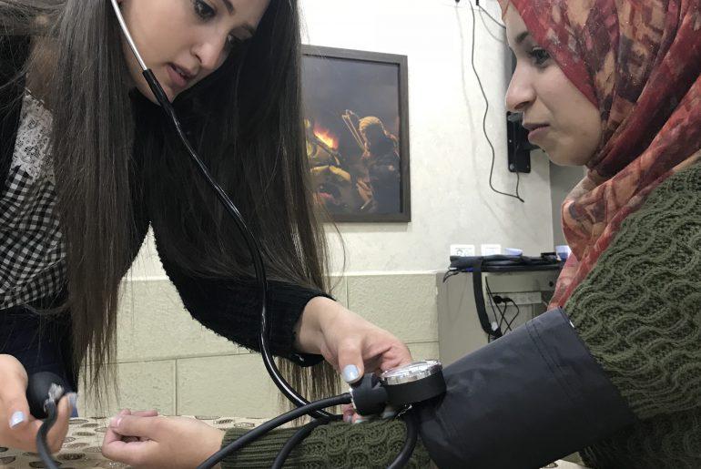 Palestinian nurse helping a patient