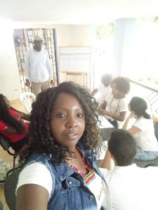 A women from AFRODES taking a photo of herself with the rest of the group behind her sitting around a table