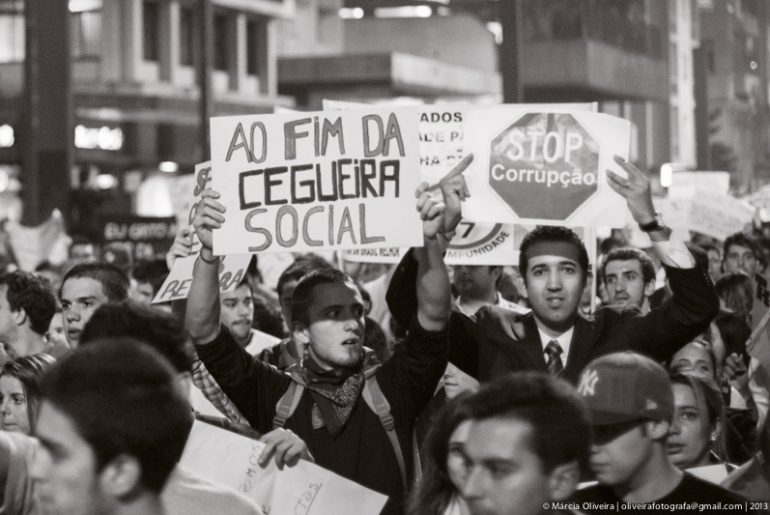 Brazilian protesters in 2013, carry signs that say To the End of Social Blindness and Stop Corruption
