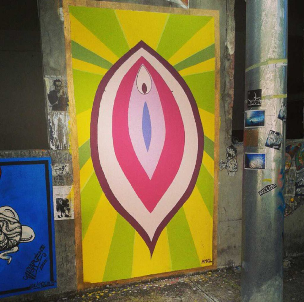 Brightly colored street mural of a vulva