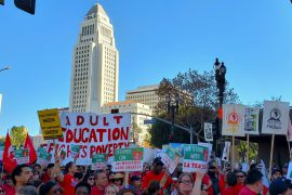A large crowd wearing red shirts and carrying protest signs at the Los Angeles Teachers Strike