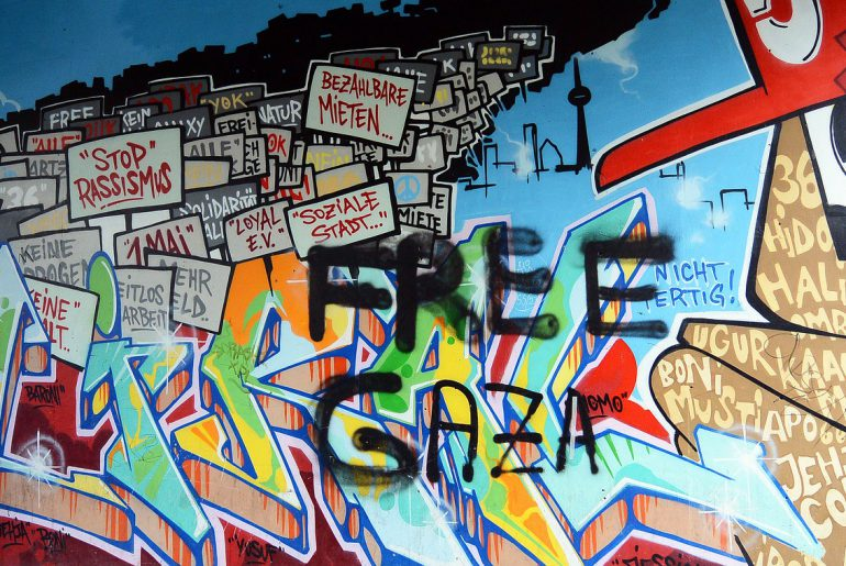 Multi-colored grafitti featuring protest signs and the words FREE GAZA