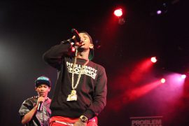 Nipsy Hussle holding a mic and singing on stage with TeeFLii, with red lights in the background