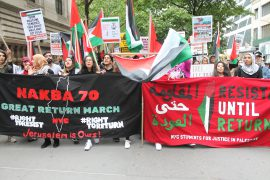 A crowd of Palestinian protests filling a street and marching with banners and signs.