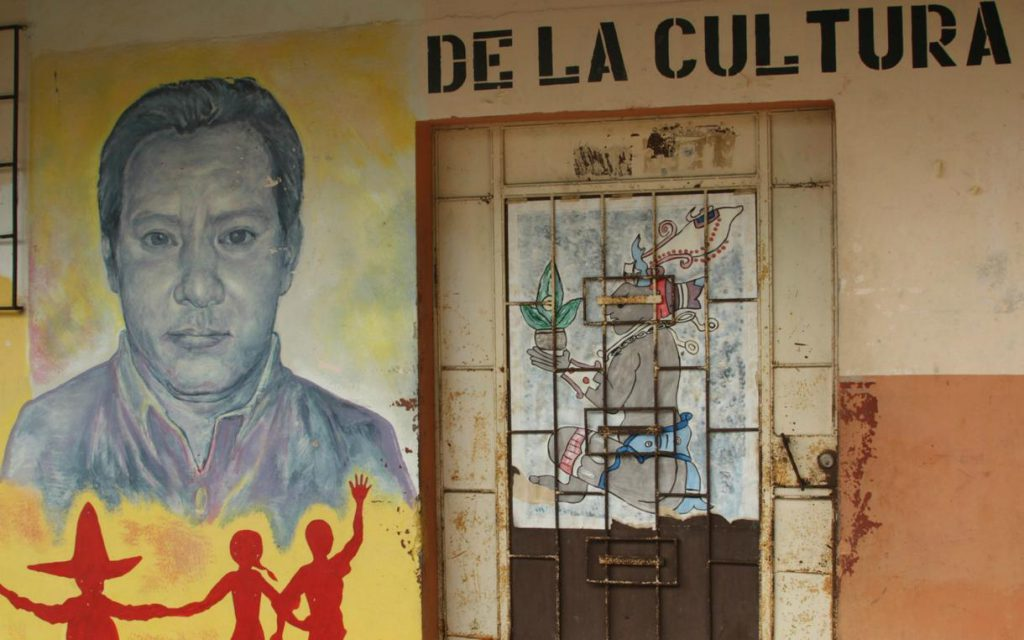 Mural on a wall of Marcelo Rivera's head and shoulders with red silhouettes of three people in the foreground, next to a door which is painted with a seated indigenous figure with elaborate headdress holding a potted plant.