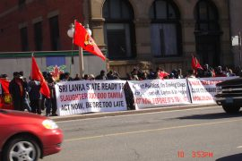 Tamil protestors holding signs and Sri Lankan flags on the side of a busy street.