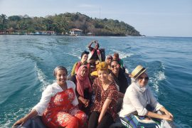 Eight women wearing colorful clothing smiling on a boat