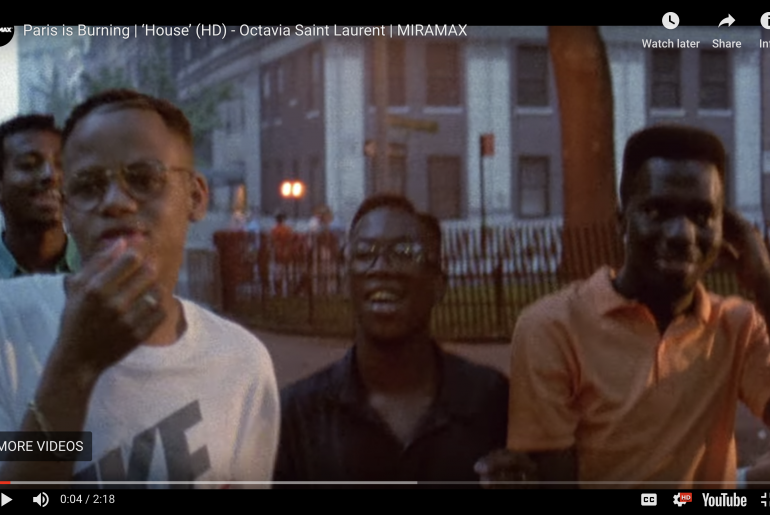 Four young black men walking down the street smiling and talking