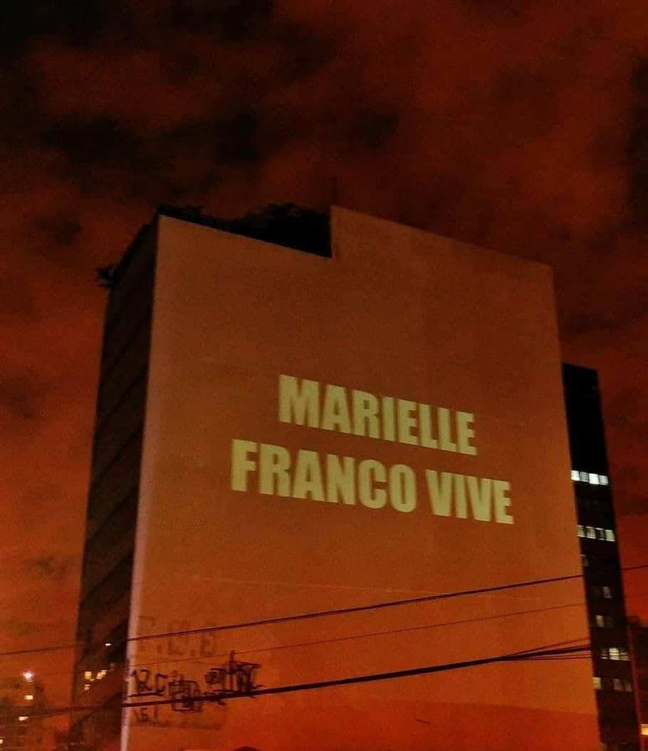 "Light projected onto the side of a building reads ""Marielle Franco Lives""."