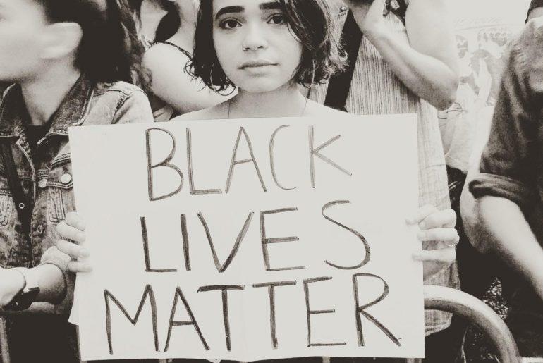 "protestor holding sign that says ""black lives matter"""