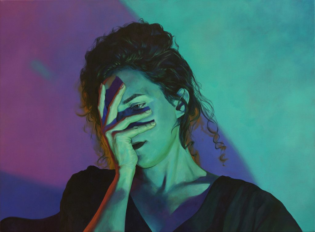 A portrait of a women bathed in turquoise light from one direction and purple light from the other. She holds her face while look downwards.