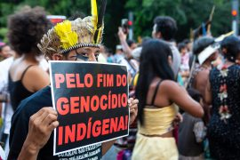 """Indian man with headdress protesting with banner """"for the end of the indigenous genocide"""", in march for the rights of the indigenous people."""