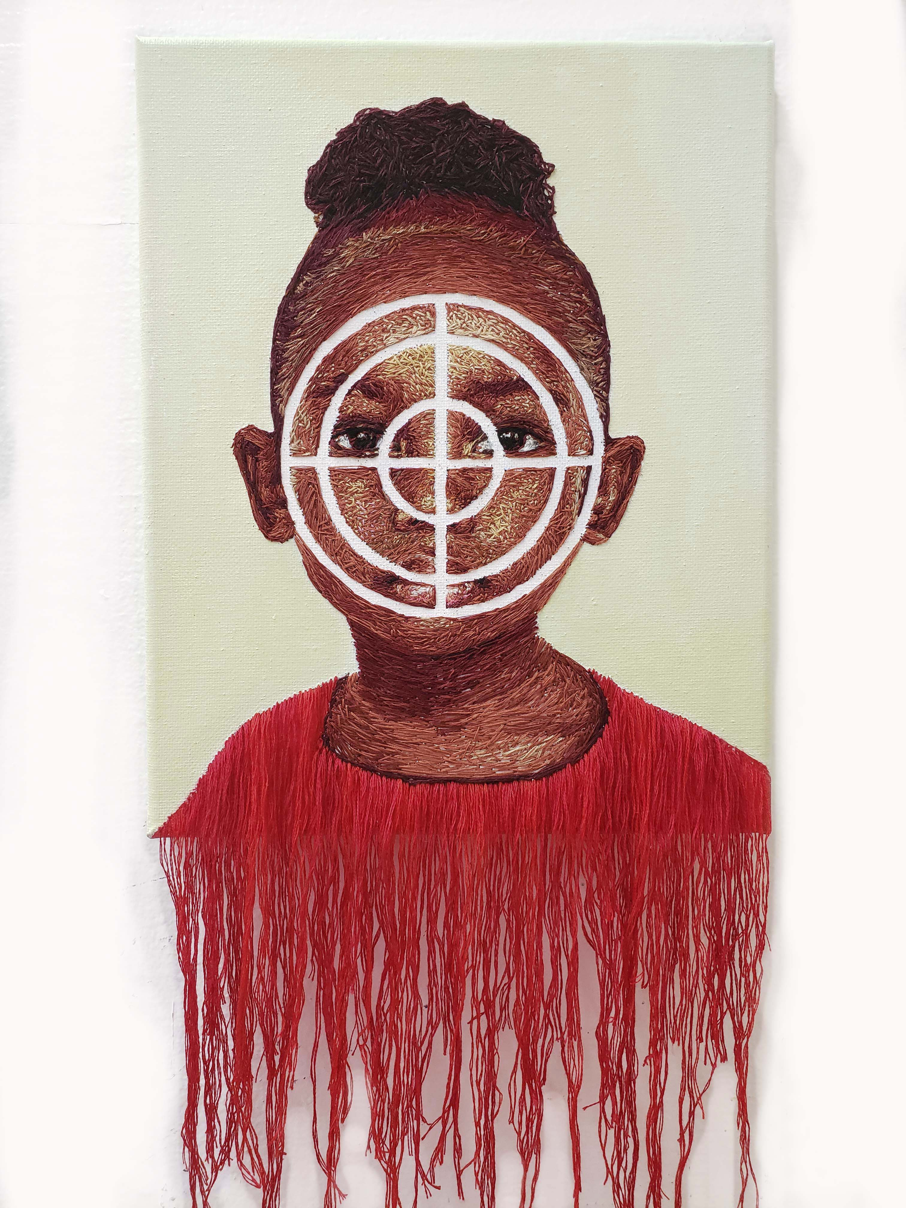 Image of hand embroidered portrait using the symbol of a Target to highlight a young girl as the victim of sexual abuse