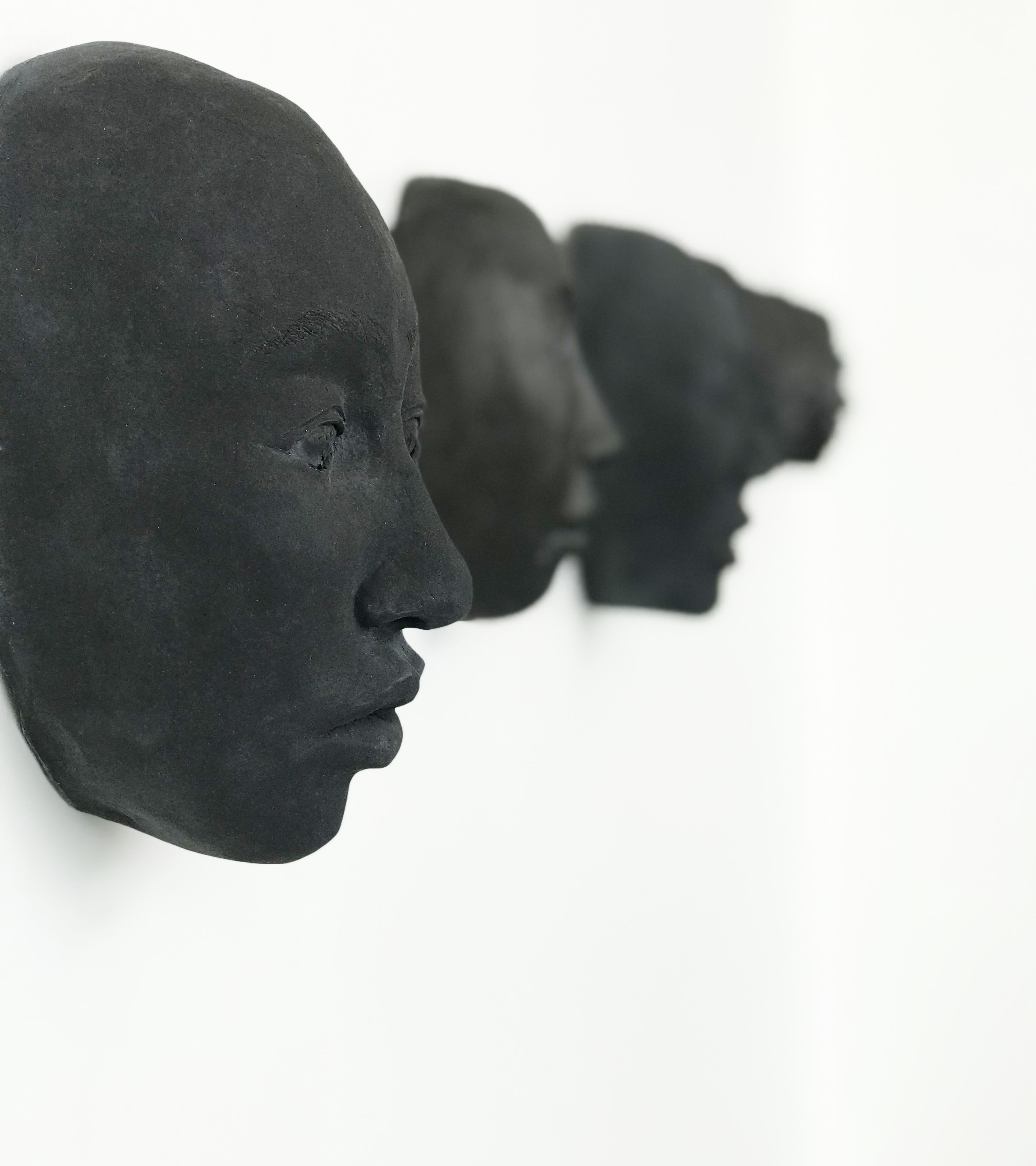an in focus black ceramic face mounted on a white wall, with a somber facial expression and similar, out of focus, black ceramic faces in the background.