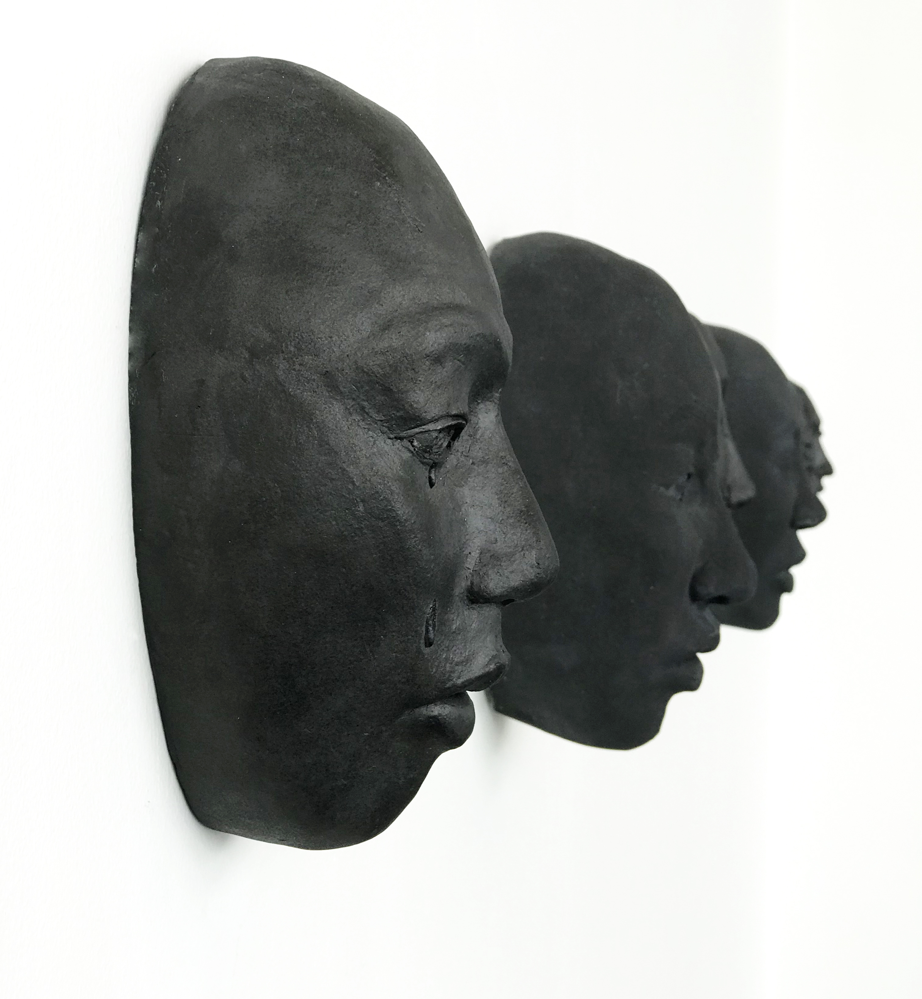 the profile of an in focus black ceramic face mounted on a white wall, with a somber facial expression and tears falling from open eyes; and the profiles of similar out of focus, black ceramic faces in the background.