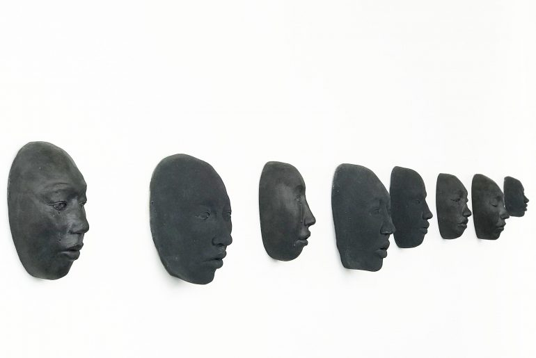 "8 black ceramic faces, mounted on a white wall below the words, ""Human Nature."""
