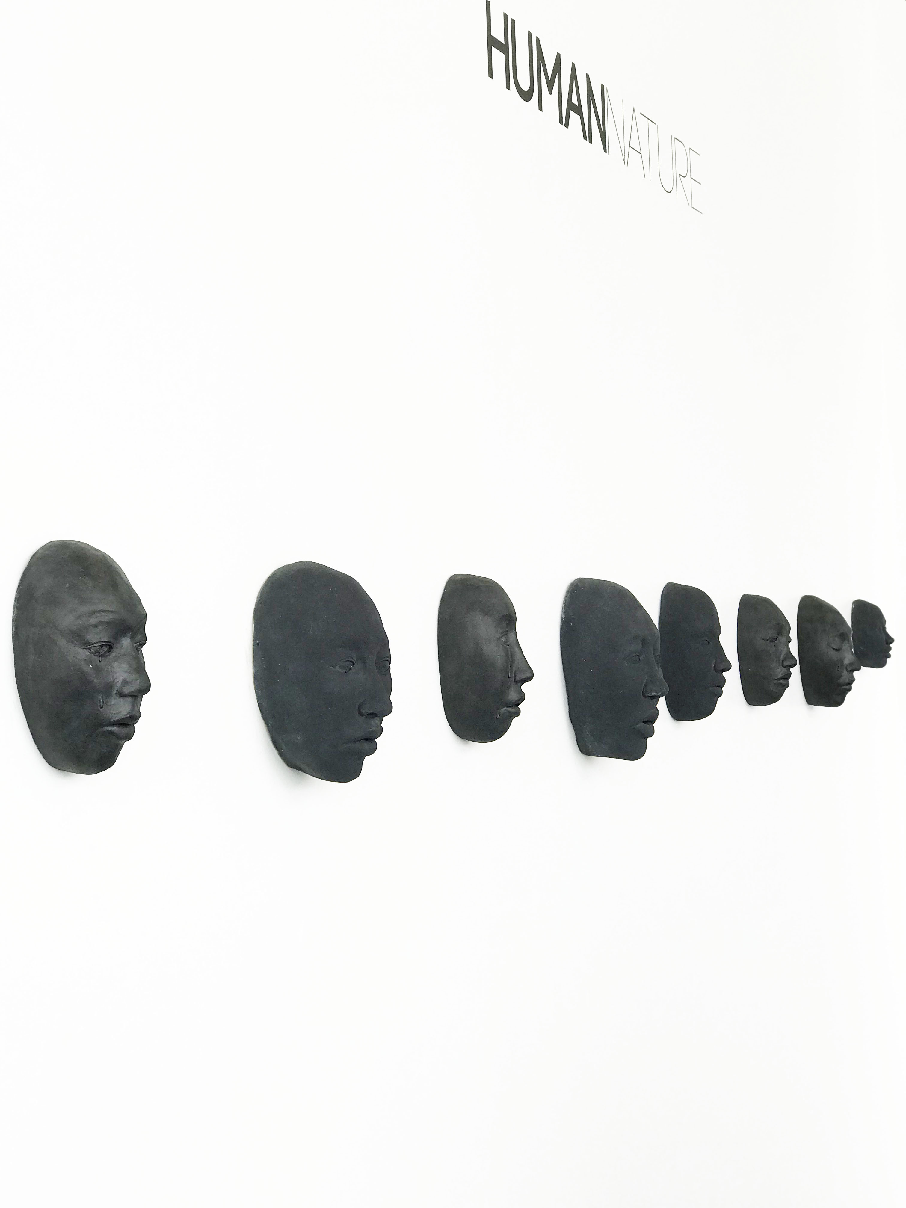 """8 black ceramic faces, mounted on a white wall below the words, """"Human Nature."""""""