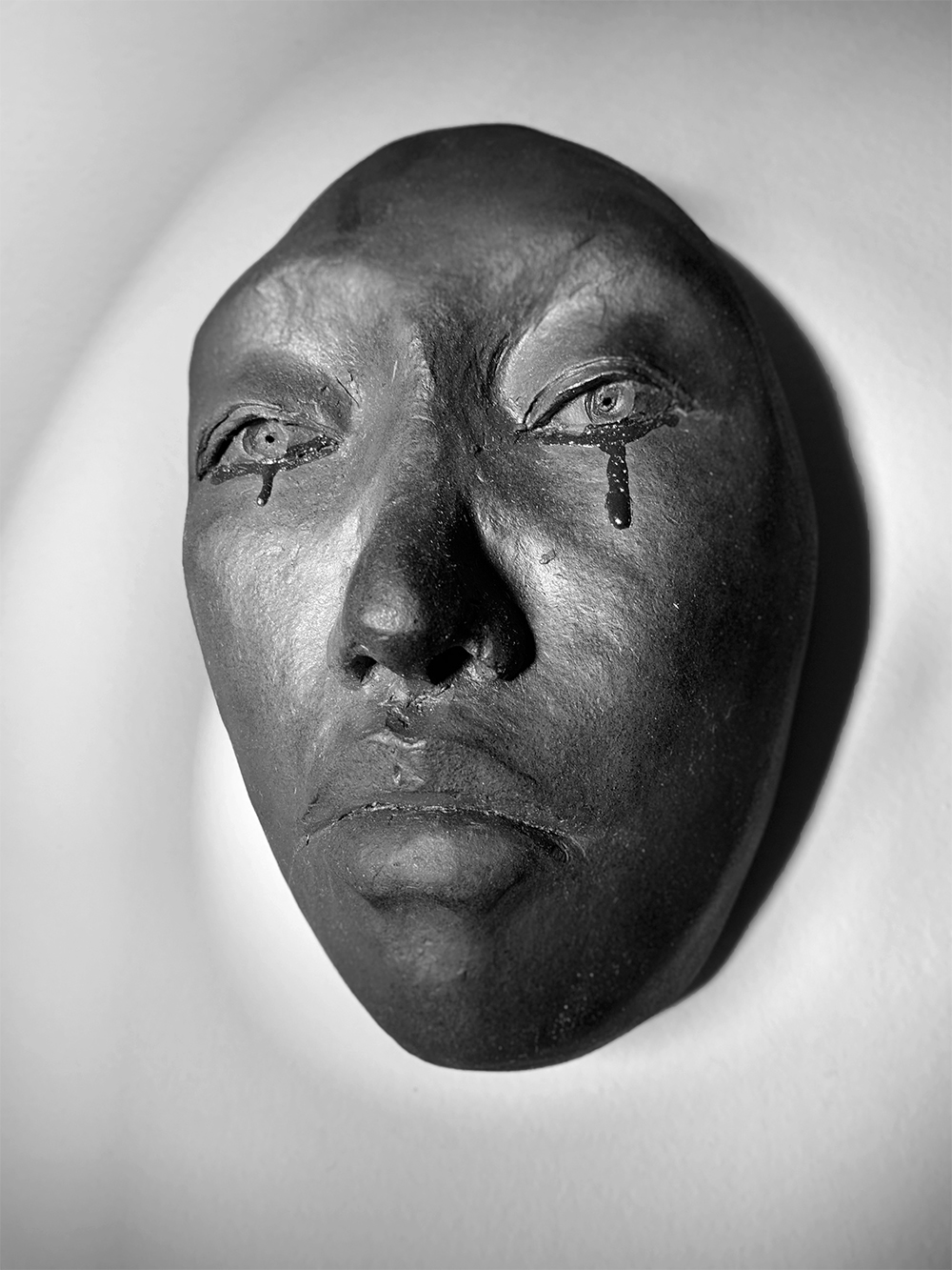 a black ceramic face mounted on a white wall, with a content facial expression and tears falling from open eyes with a closed mouth.
