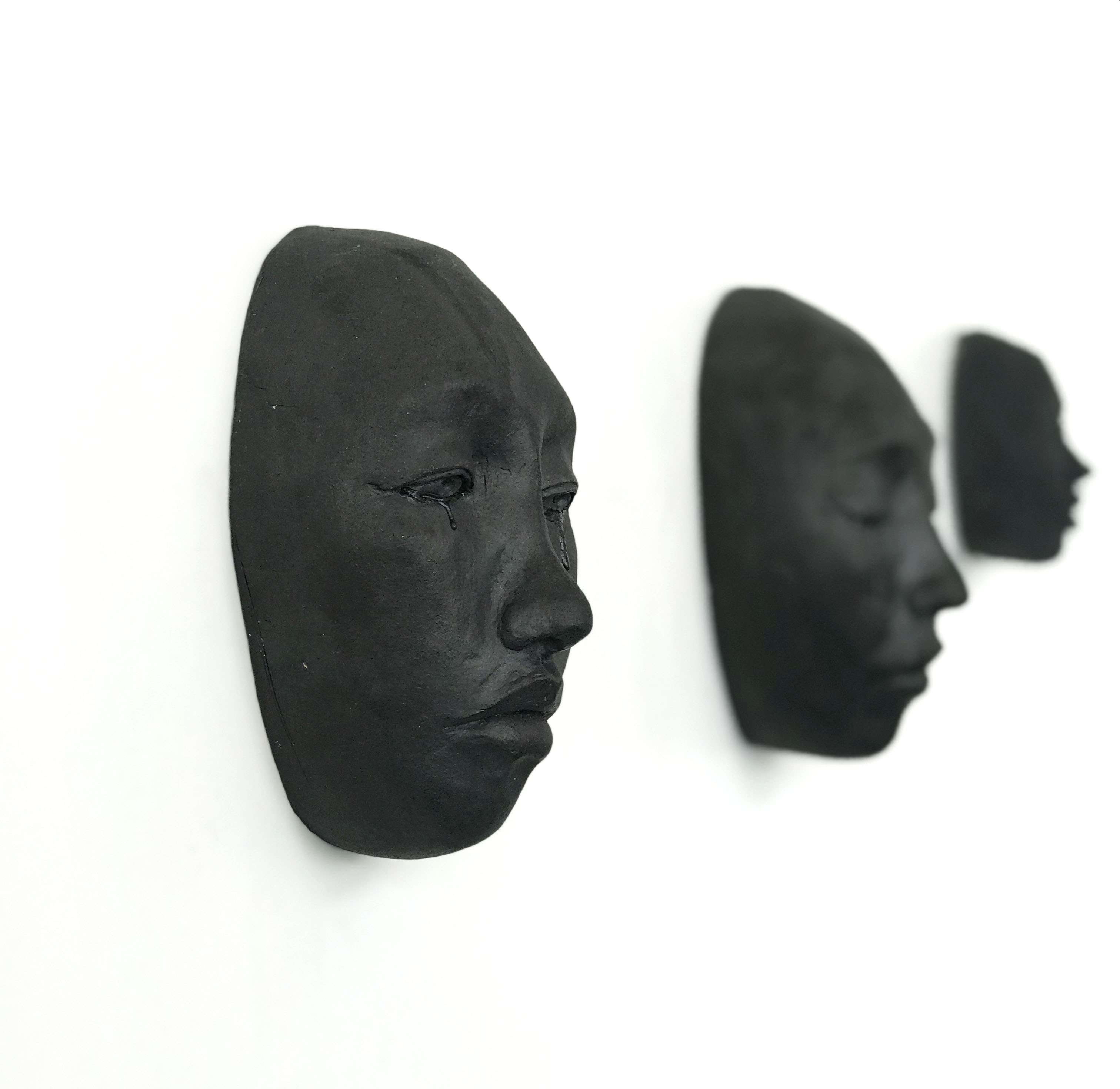 an in focus black ceramic face mounted on a white wall, with a somber facial expression and tears falling from open eyes; and two similar out of focus, black ceramic faces in the background.