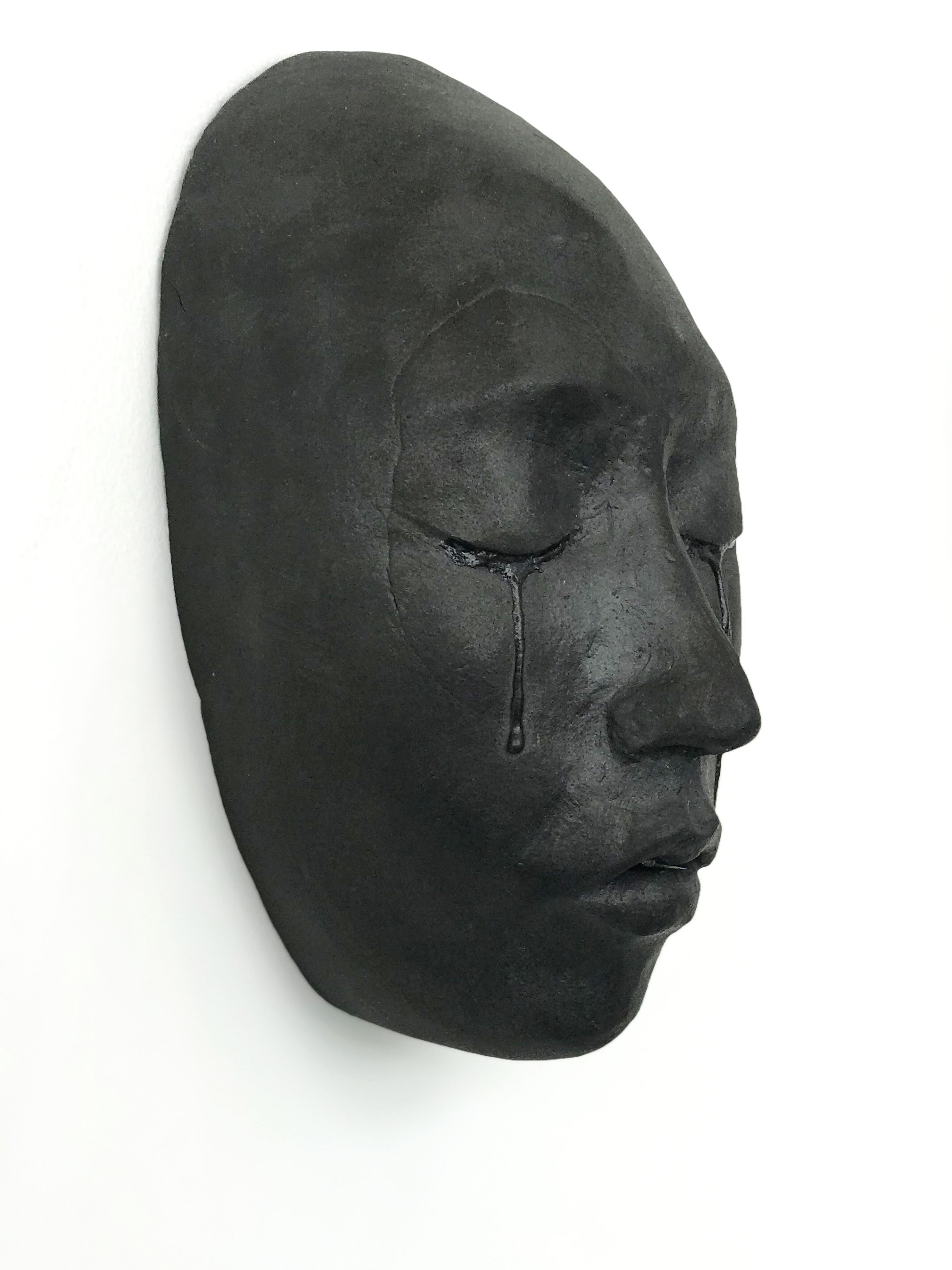 a black ceramic face mounted on a white wall, with a regretful facial expression and tears falling from closed eyes with a closed mouth.