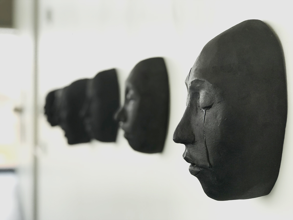 an in focus black ceramic face mounted on a white wall, with a regretful facial expression and tears falling from closed eyes; and similar out of focus, black ceramic faces in the background.
