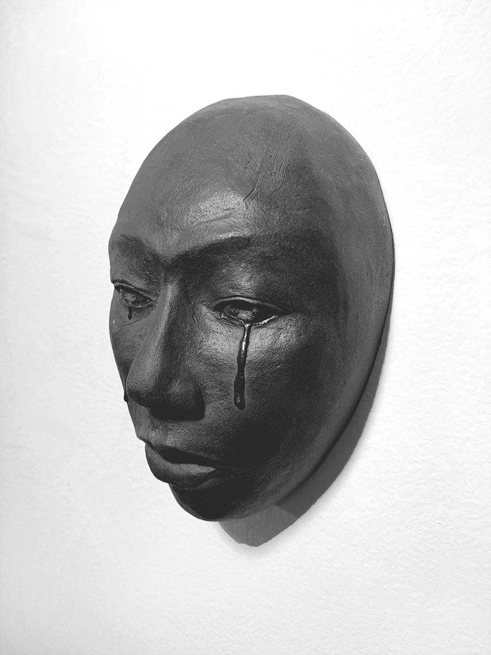 a black ceramic face mounted on a white wall, with a focused facial expression and tears falling from open eyes with a closed mouth.