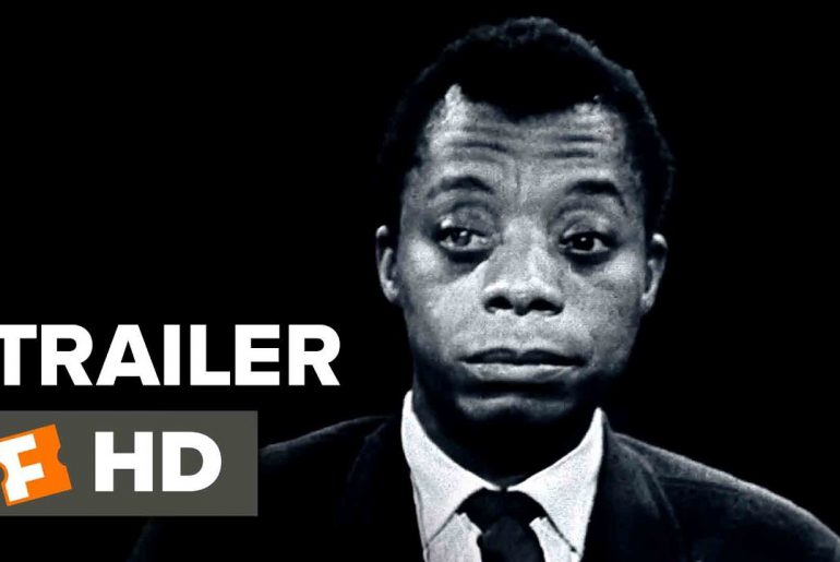black and white head shot picture of James Baldwin wearing a suit and tie