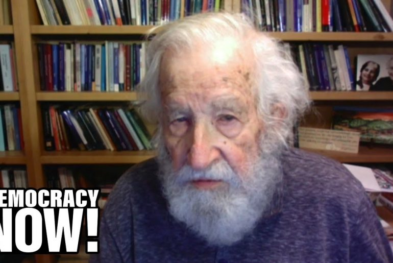 """Noam Chomsky with a bookshelf in the background, with """"Democracy Now!"""" written on the foreground."""