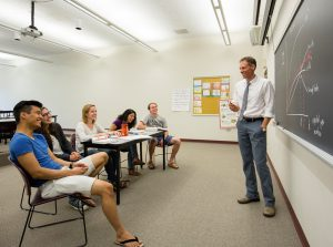 Economics Professor Patrik Hultberg teaches students from a blackboard